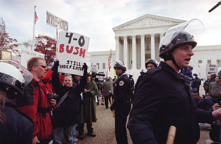 Protesters hold pro-Bush signs while police do crowd control, with Supreme Court in the background