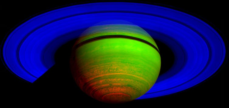 Image of Saturn with false colour enhancement. The rings are bright blue and the planet itself a neon green with flourescent orange toward the bottom left-hand side of the planet.