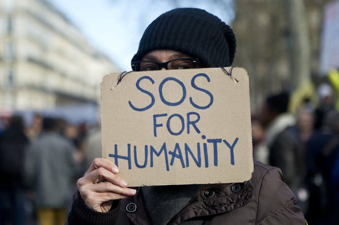 friday essay reflections on the idea of a common humanity a w holds a sign at a protest in paris in 2016 elyxandro cegarra new zulu