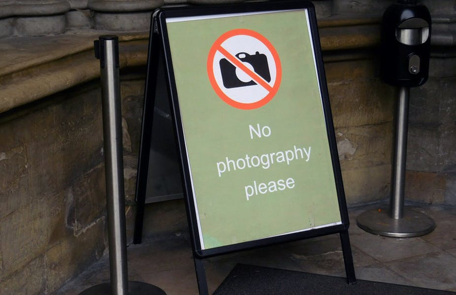 Why is taking photographs banned in many museums and historic places?
