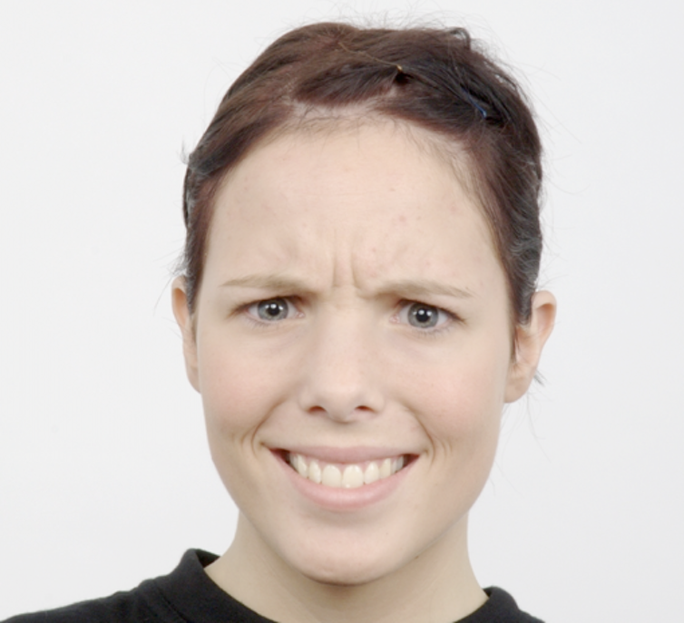 A woman's face is looking directly at the camera with angry eyes and a smiling mouth. She has dark hair tied up and pale blue-grey eyes.