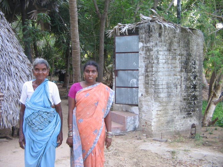 A Tamil woman and her mother-in-law in front of their toilet whose roof caved in - hence the thatch. FAL