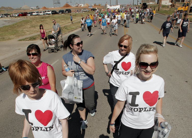 a 2012 ceremony, residents of Joplin, Missouri walk the route of a massive tornado that ripped through the town a year earlier, killing 161 people