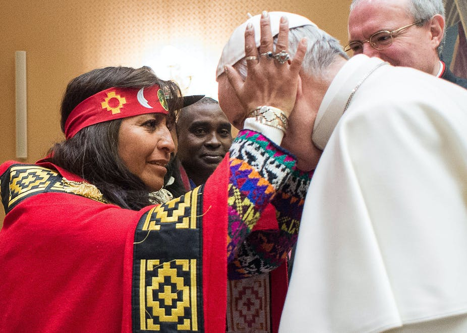 What makes a mountain hill or prairie a sacred place for native a woman holds pope francis head during his meeting with representatives of indigenous peoples at the vatican on feb 15 2017 losservatore romanopool freerunsca Images