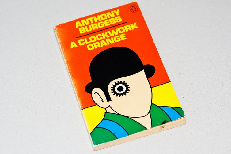 A picture of the book 'A Clockwork Orange' is shown on a grey background. The author and title are at the top and written in yellow text against an orange background. There is a graphic of a man in a bowler hat on the front, wearing a green and blue top. The face only has one feature, which is an eye with cog decor around it.
