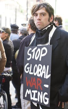 A man looking at the camera with a sign around his neck reading 'Stop Global Warming'