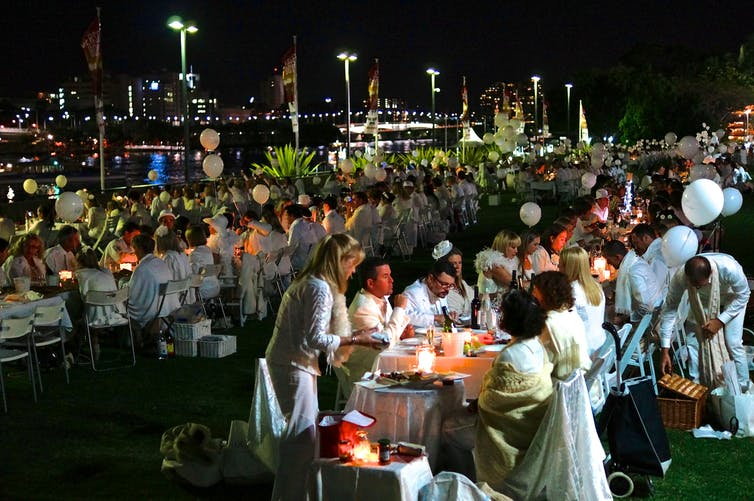 People eating dinner at long tables dressed in white