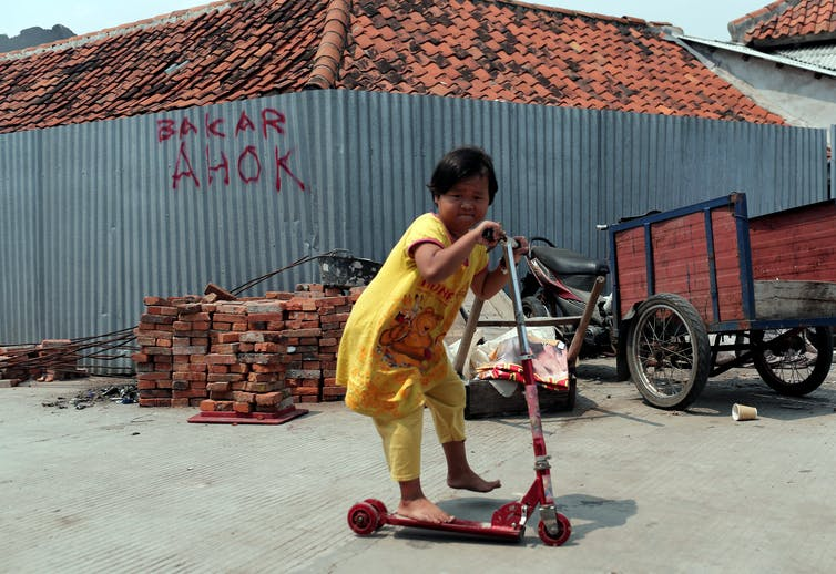 A child plays in front of a wall with a slogan 'burn Ahok' in Jakarta. (Reuters Photo/Beawiharta)