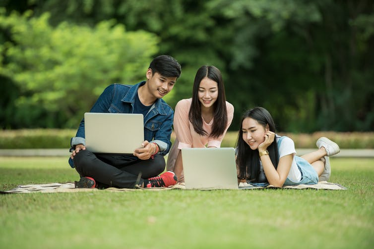 Three Asian students sitting on a blanket in a park looking at laptops