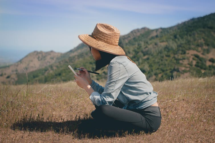 Young woman with a sunhat sitting in a field writing in a notebook