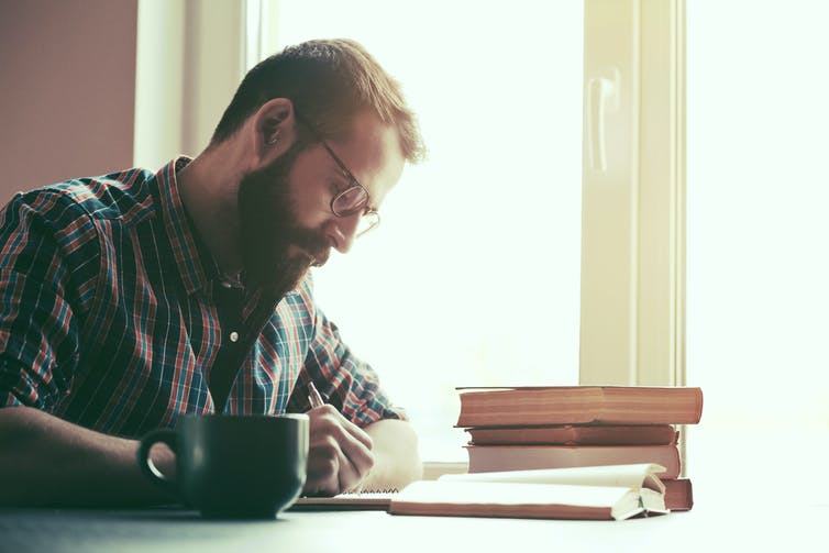 Man with a beard and check shirt writing in a notebook surrounded by books and a black mug