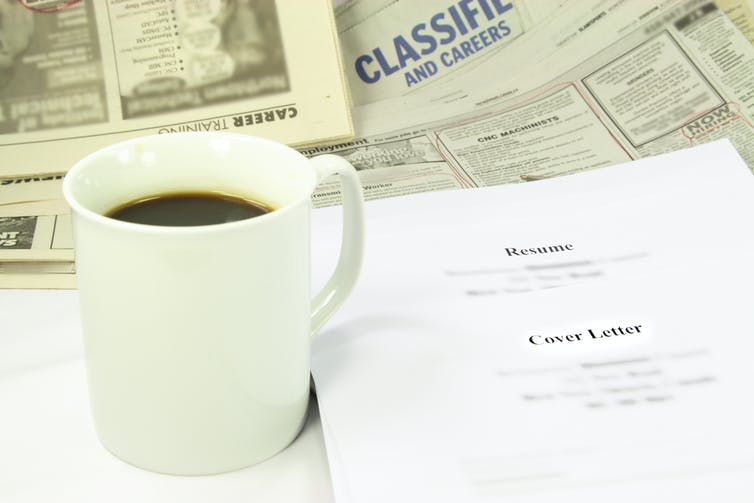 A table covered with a white coffee cup, newspapers, a resume and CV