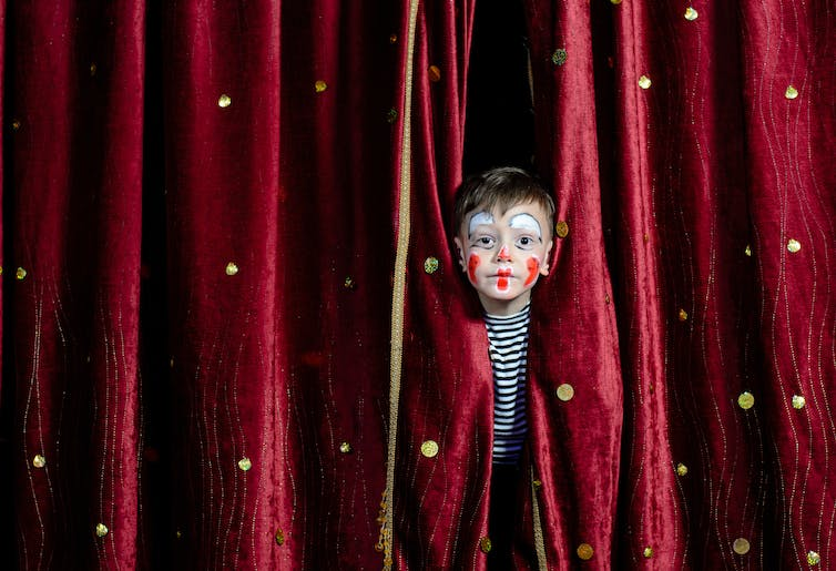 little clown looking through theatre's curtains