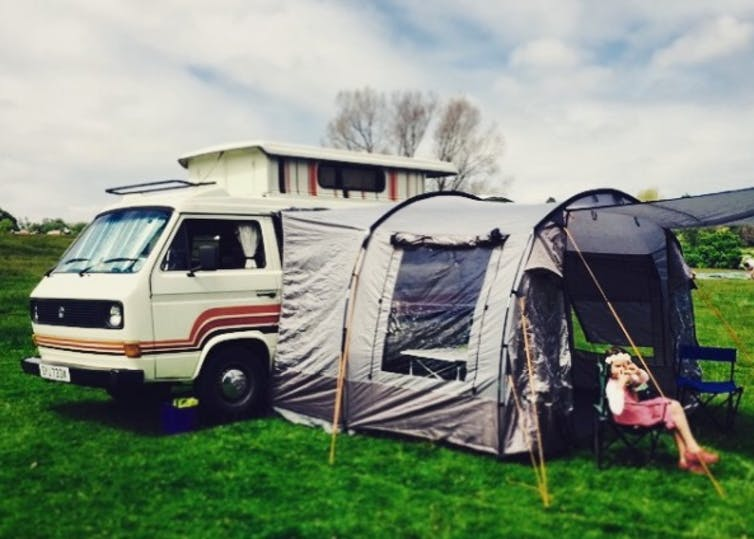 A VW van stands on a field with a tent attached.