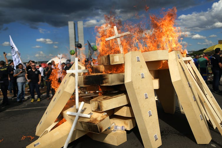 Striking police officers set fire to faux coffins during a protest against pension reforms proposed by President Michel Temer in April 2017. Adriano Machado/Reuters