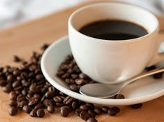 Image of a cup of coffee & cofee beans