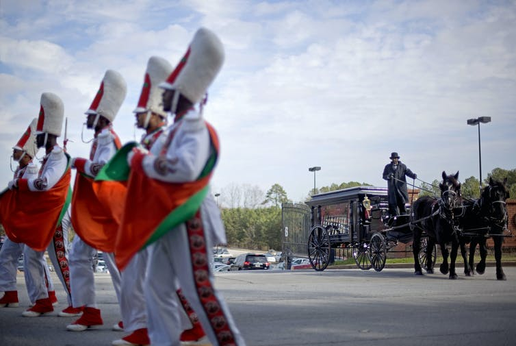 The Florida A&M marching band escorts the casket of band member Robert Champion, who died after a band hazing incident in 2011. Twelve members of the band were charged in relation to the death. (AP Photo/David Goldman)