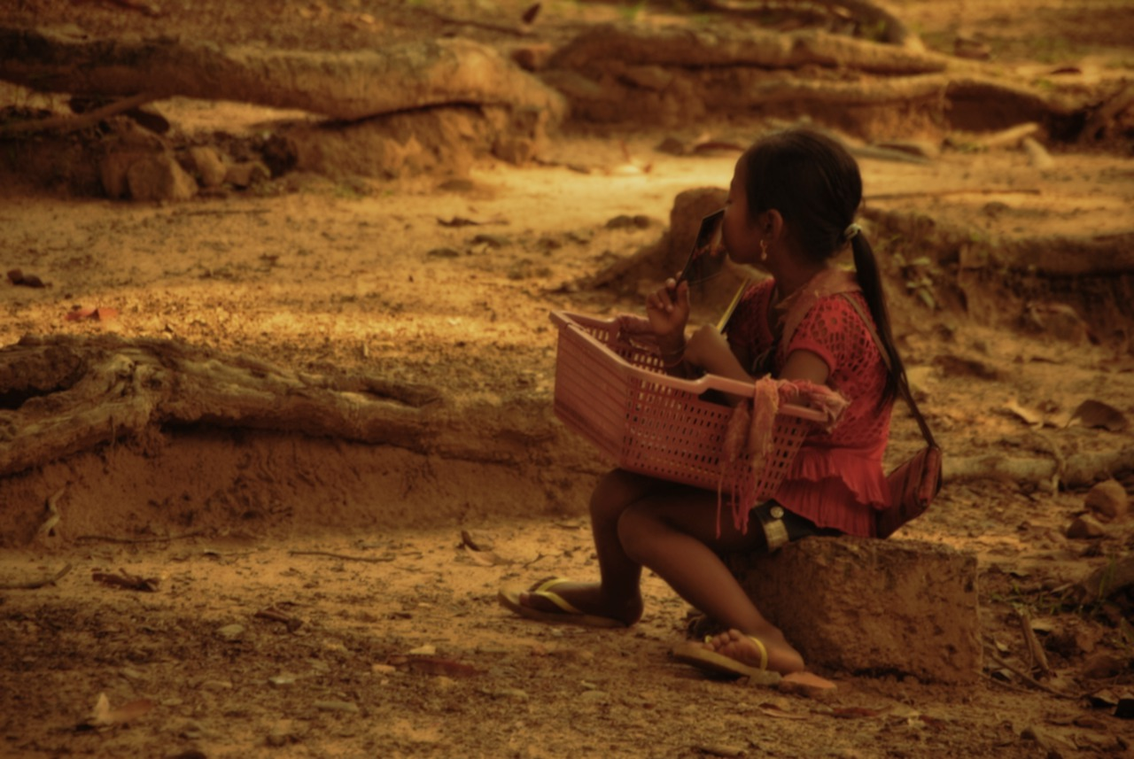 Young girl with a basket sitting on some dry land