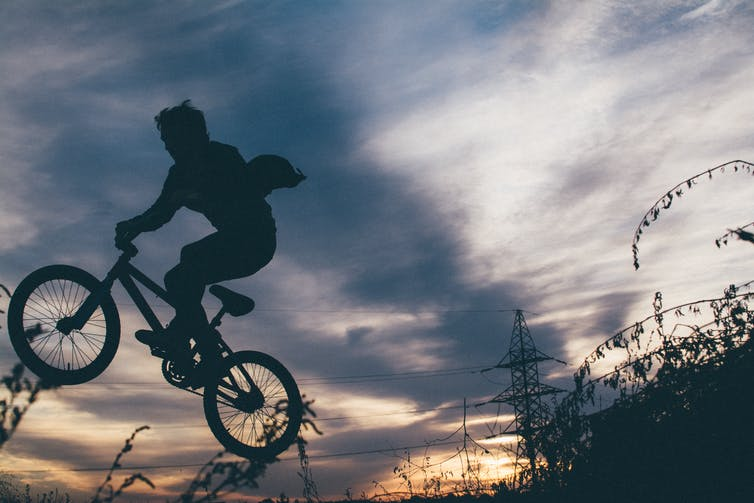 "Image of a boy on a bike doing ""jumps"""