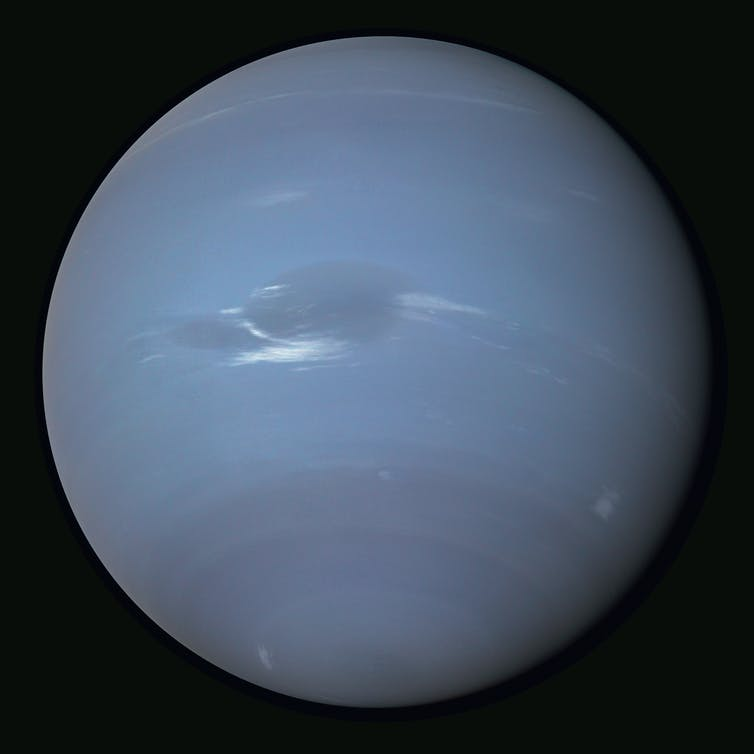 Neptune's bright wispy cirrus-type clouds can been seen against the blue atmosphere.