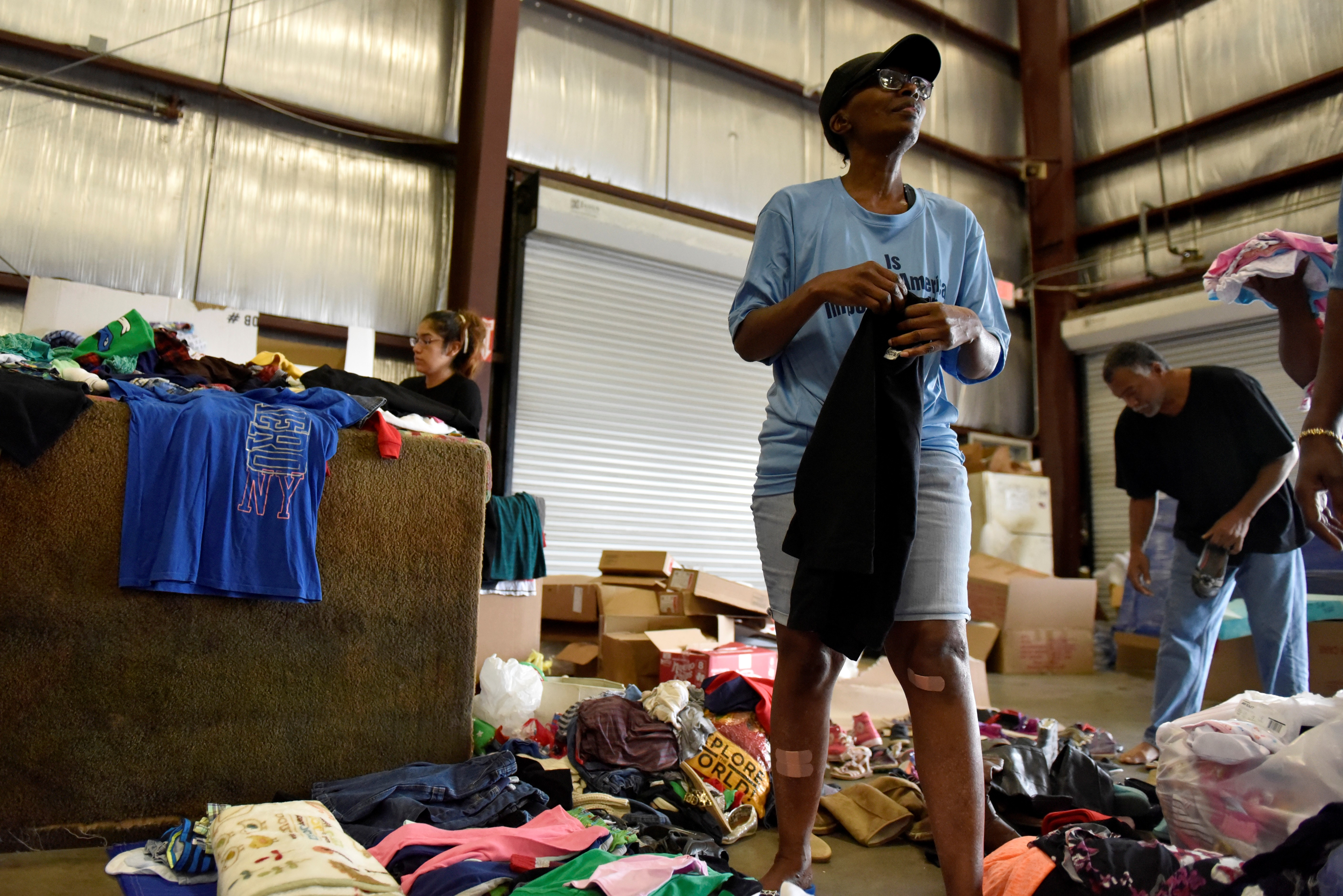 Evacuee Carolyn Jackson sorts through donated clothing in Houston.  Reuters/Nick Oxford