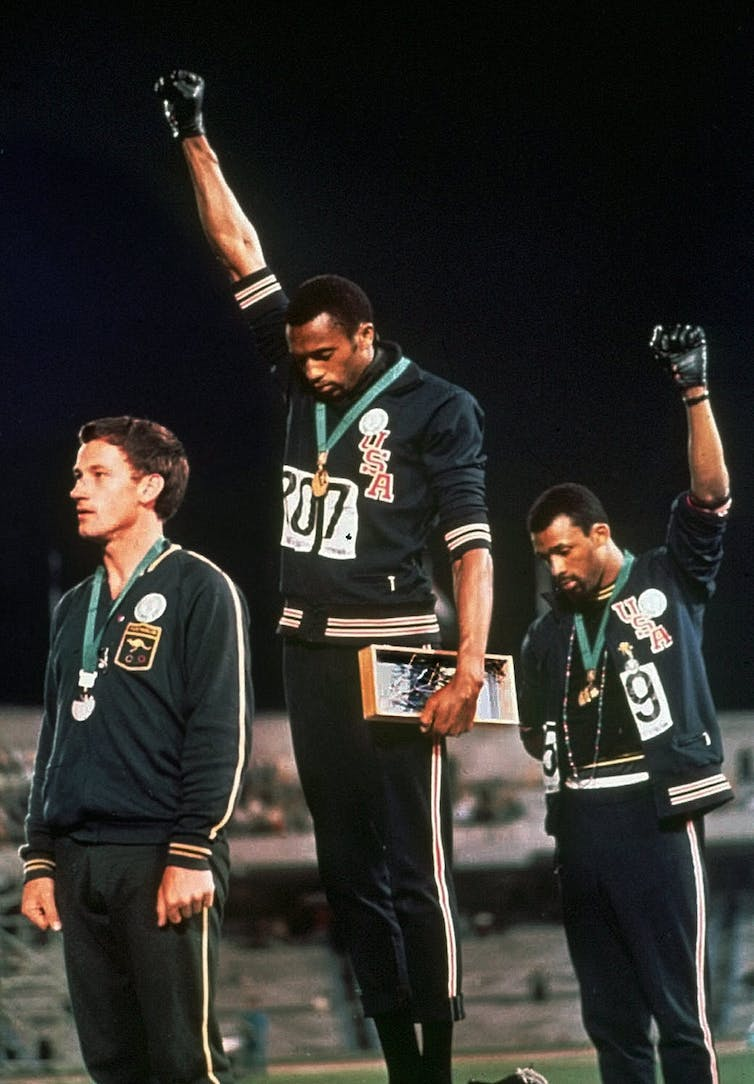 Australian Peter Norman, left, supported the Black Power protests of U.S. athletes Tommie Smith, centre, and John Carlos during the medal ceremonies for the 200 metre sprint at the 1968 Olympics. (AP Photo)
