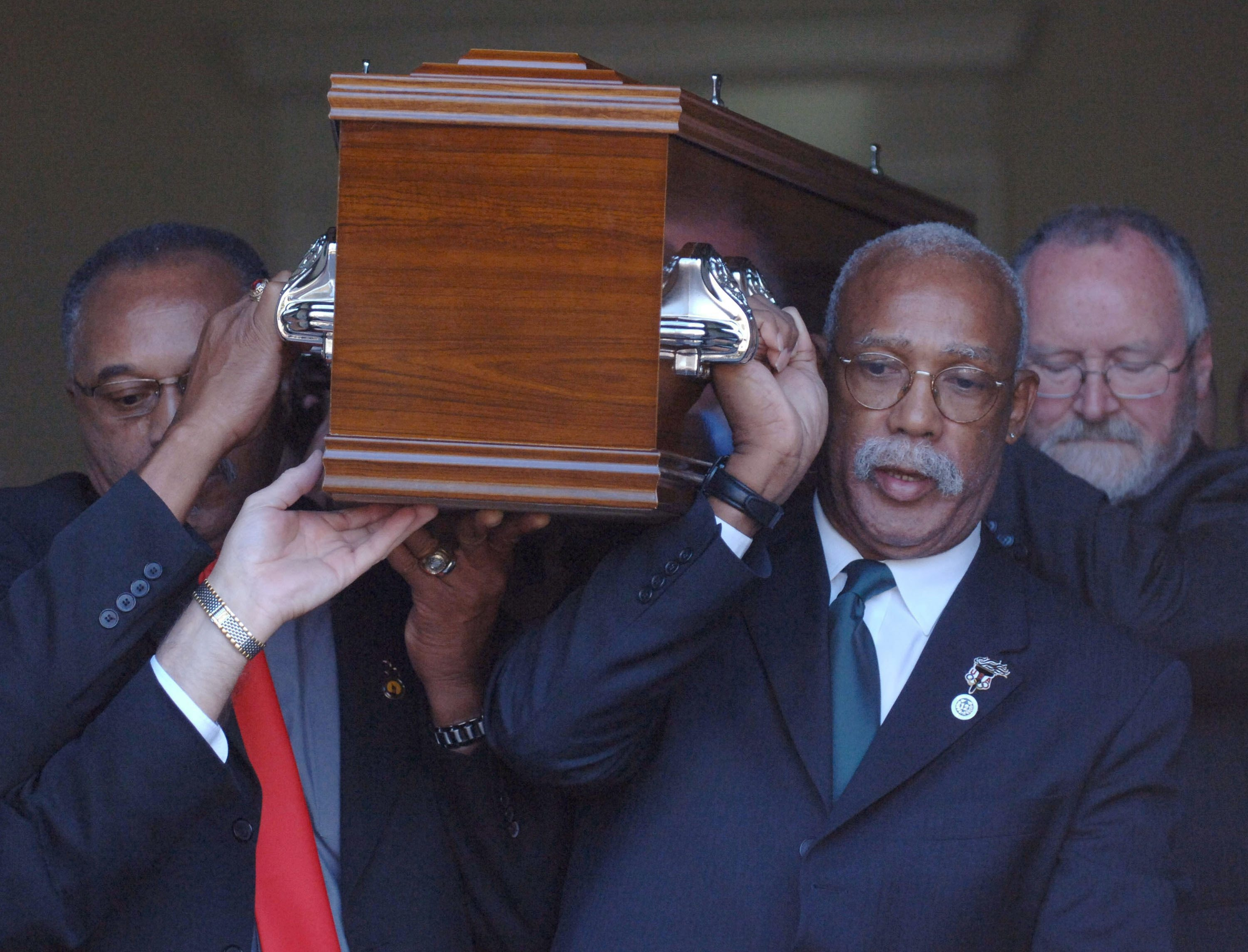 Tommie Smith, left, and John Carlos, right, who gave the historic Black Power salutes at the 1968 Olympics, reunite for the final time with the third man on the podium that year as they as they act as pallbearers for Peter Norman at his funeral in Melbourne, Australia in 2006. (AP Photo)