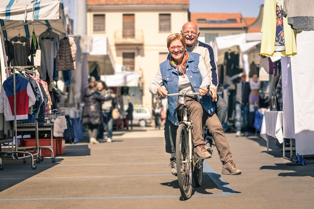 Picture of an older couple sharing a bike