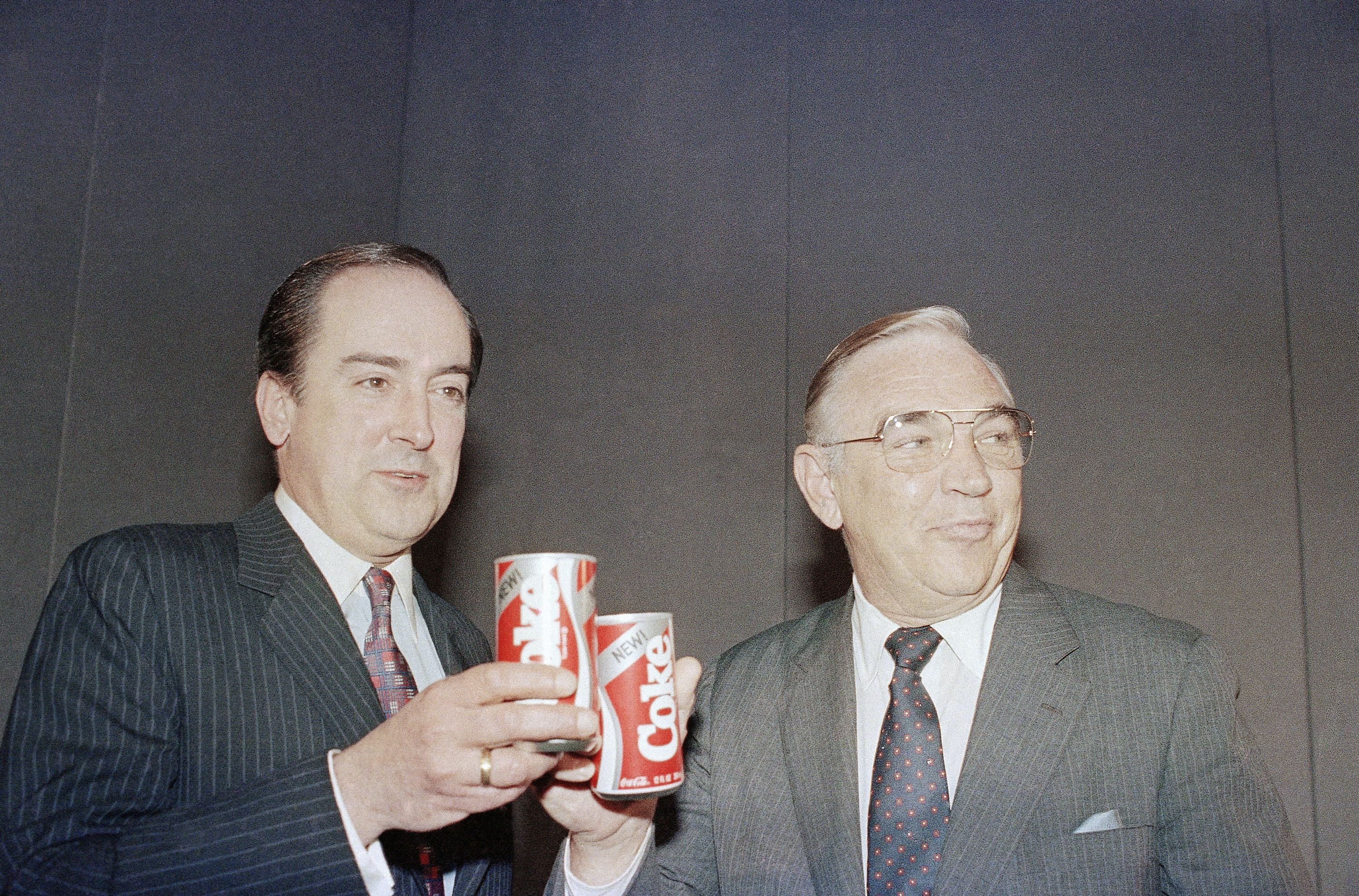 Coca-Cola executives Robert C. Goizueta and Donald R. Keough toast cans of 'New Coke' – a product rollout that's considered one of the biggest business blunders of all time.