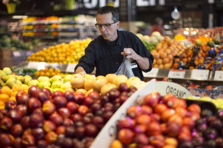 Grocery store employee gathers apples for an online order.