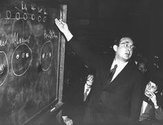man pointing at a chalkboard with formulas