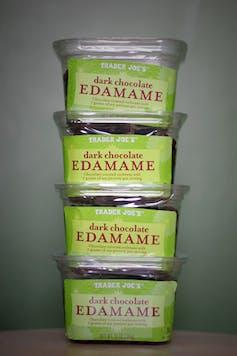 Containers of dark chocolate edamame