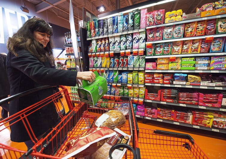 Woman shopping in grocery store places a six pack of beer in her grocery cart.