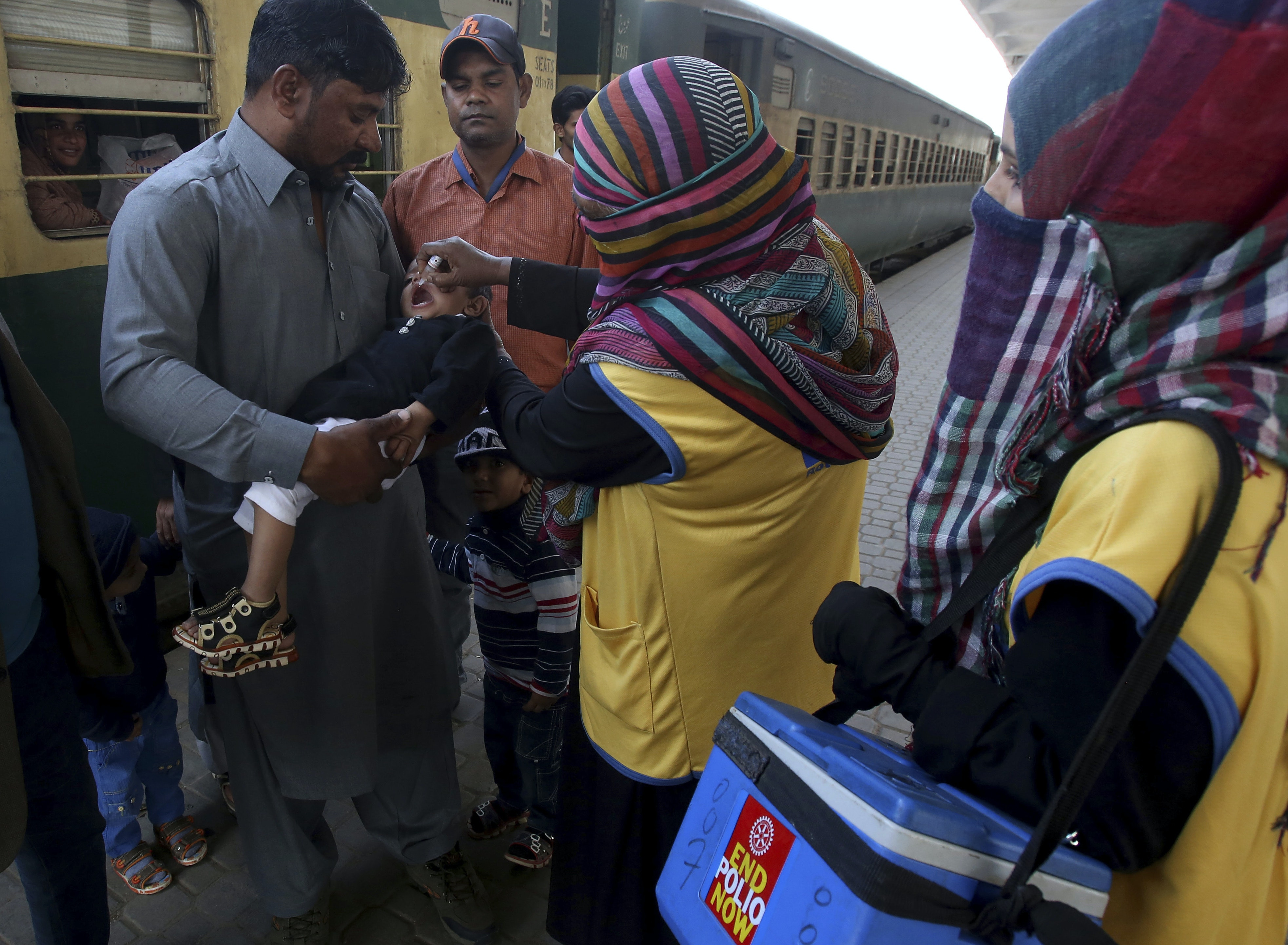 A health worker gives a polio vaccine to a child at a railway station in Pakistan. AP Photo/Fareed Khan