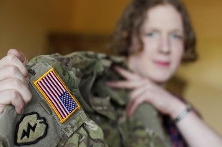 Transgender U.S. Army Capt. Jennifer Sims lifts her uniform