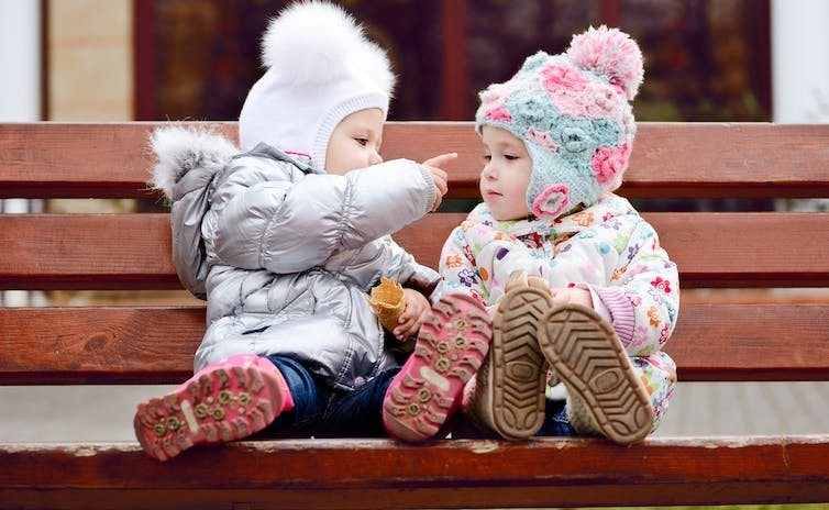 children-taking-to-each-other-on-a-bench