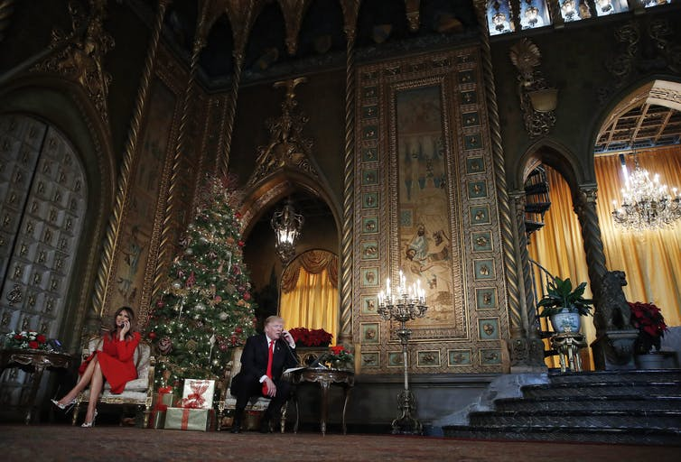 U.S. President Donald Trump and First Lady Melania Trump speak on the phone with children as they track Santa's movements with the North American Aerospace Defense Command (NORAD) Santa Tracker on Christmas Eve at the president's Mar-a-Lago estate in Florida in December 2017. (The Associated Press)