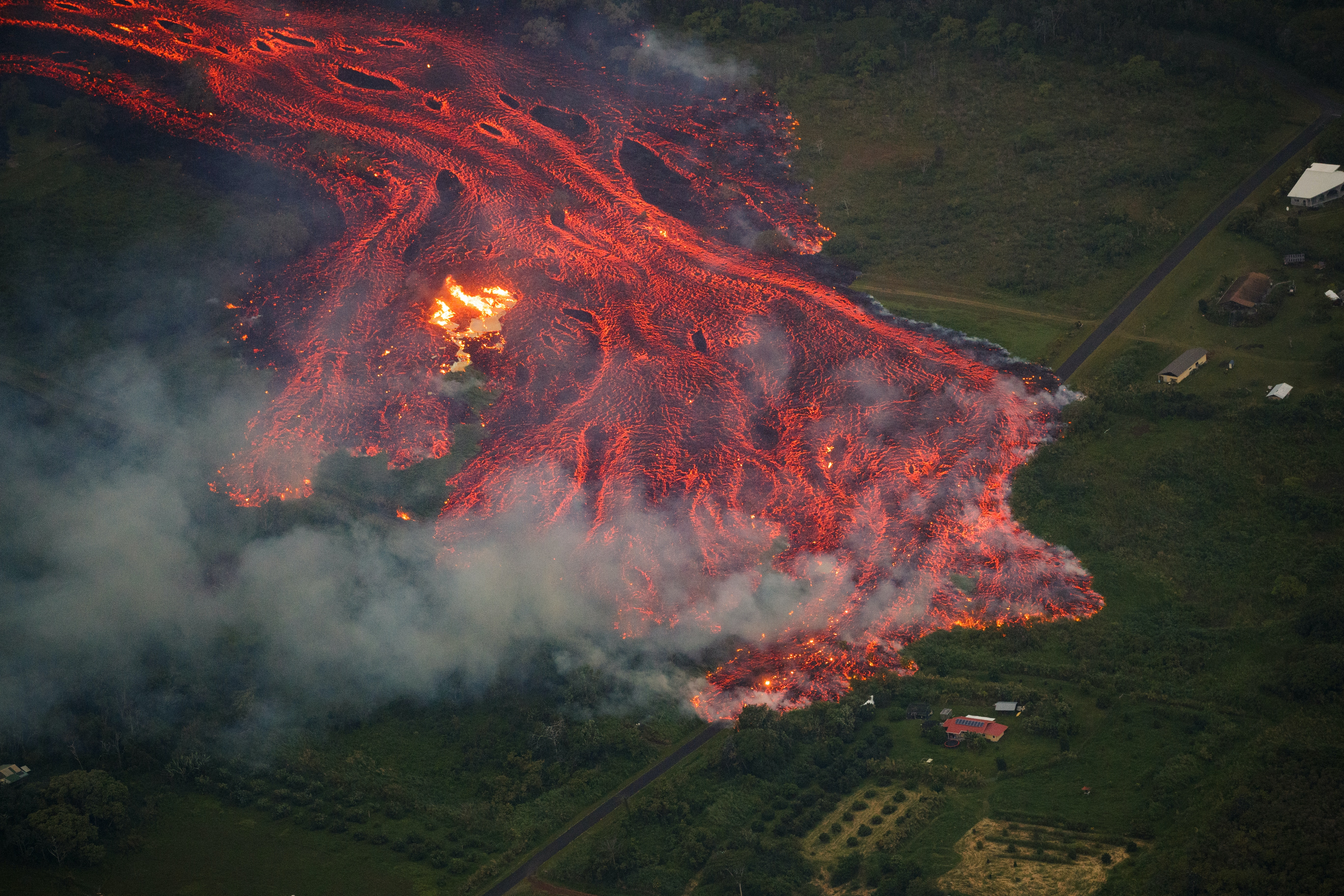 Lava in Hawai'i is reaching the ocean, creating new land but also corrosive acid mist