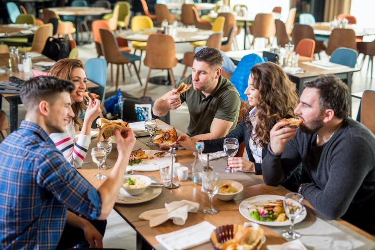 A group of people sitting around a restaurant table eating pizza.