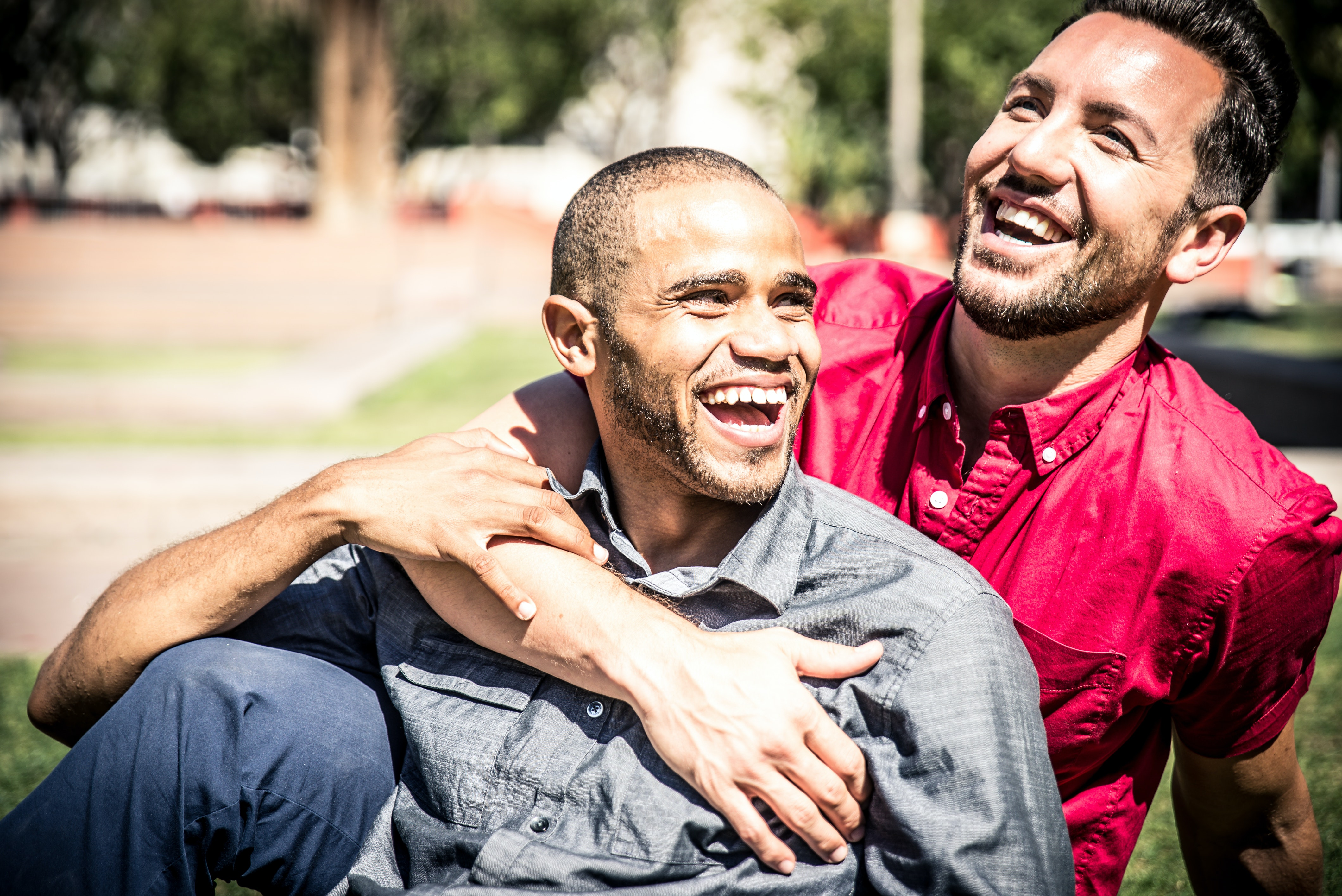 Two men sit in a sunny park and hug each other. They are laughing.