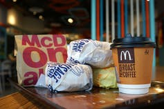 A McDonalds meal consisting of a coffee and three burgers.