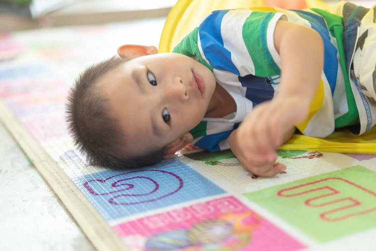 multilingual-child-lying-on-mat