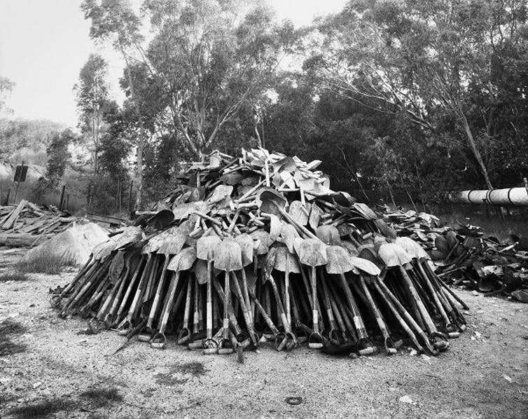 Lashing shovels retrieved from underground. Every grain of sand in the yellow tailings dumps that made the Witwatersrand landscape and every grain of gold that made its wealth, came from a rock off a black man's shovel underground. Central Salvage Yard, Randfontein Estates, Randfontein, 1966. Credit: David Goldblatt