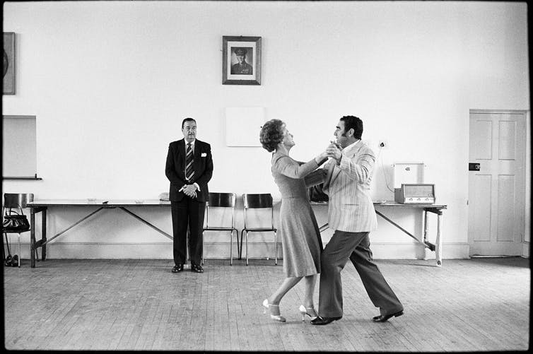 Dancing-master Ted van Rensburg watches two of his ballroom pupils, swinging to a record of Victor Sylvester and his Orchestra, the MOTHS' Hall at the old Court House, Boksburg. 1980. Credit: David Goldblatt