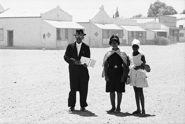 An elder of the Dutch Reformed Church walking home with his family after the Sunday service, Carnavon, Cape Province (Cape), January 1968. Credit: David Goldblatt