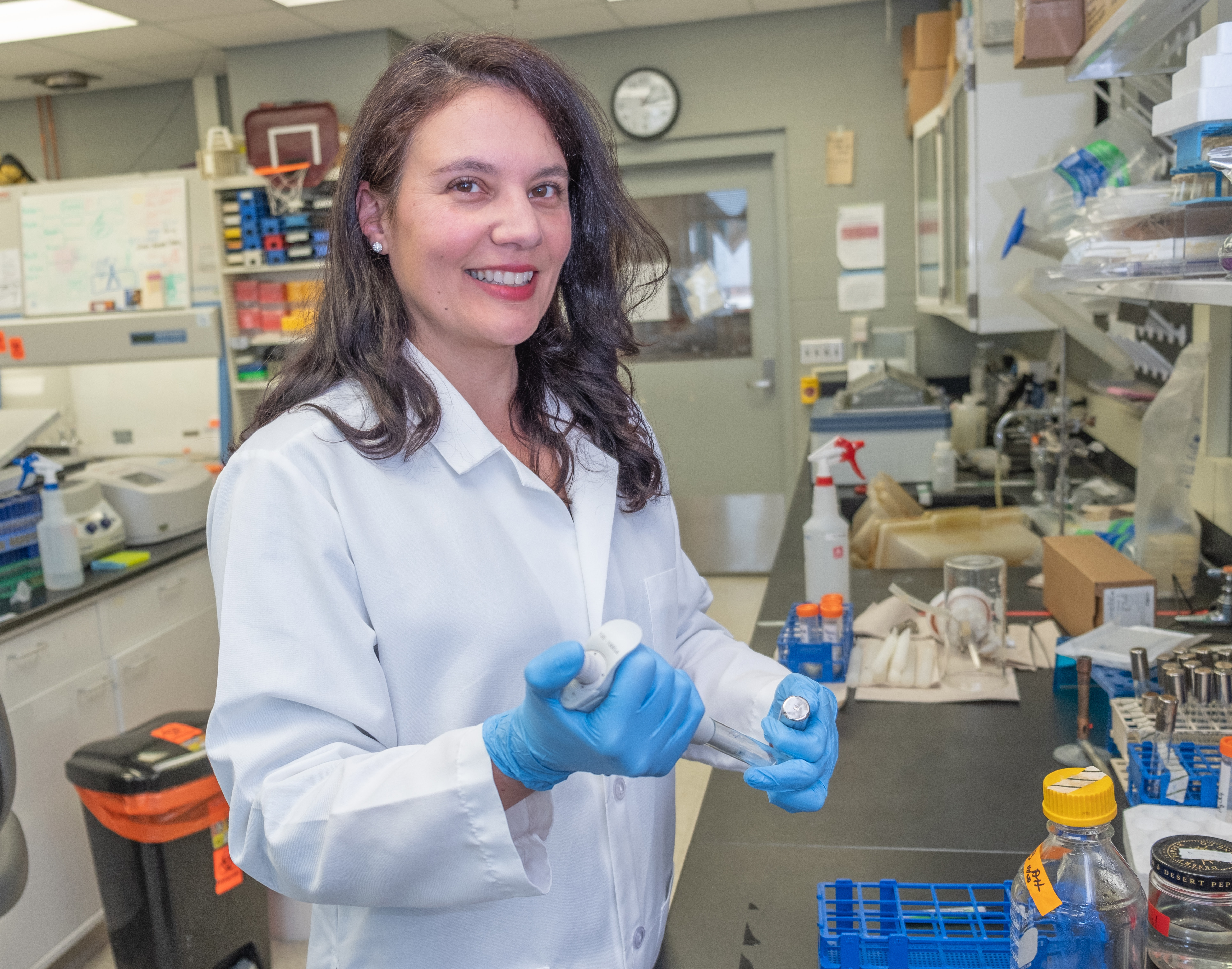 Alessandra Agostinho Hunt measures biofilm formation of Psuedomonas aerugionsa by pipetting in the purple dye crystal violet to stain the microbial structure.