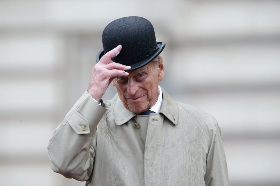 Prince Philip wearing and tipping a bowler hat.