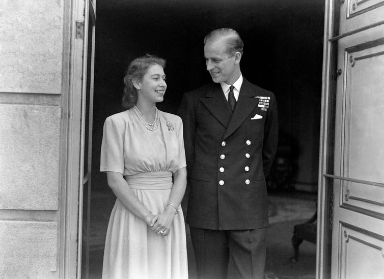 Black and white photo of Philip and Elizabeth stood smiling in doorway