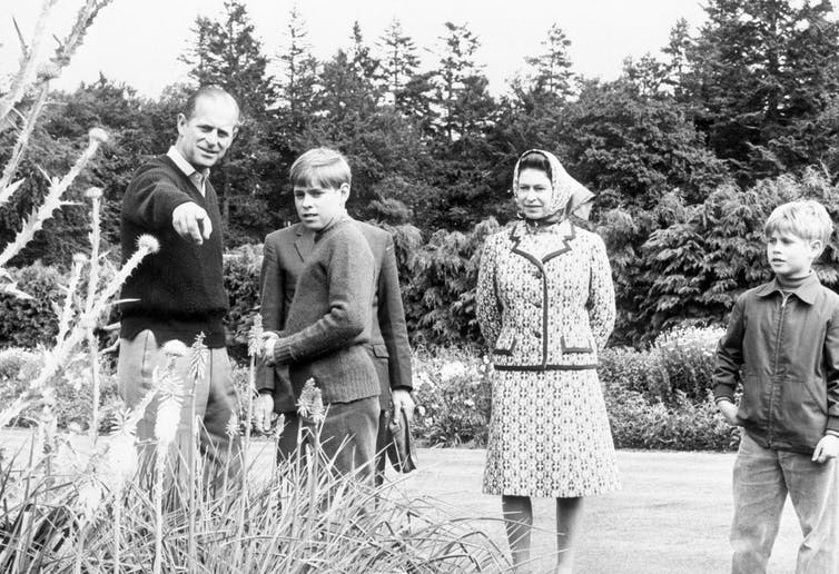 Black and white photo of middle aged Philip and Queen Elizabeth with princes Andrew and Edward as children admiring the garden