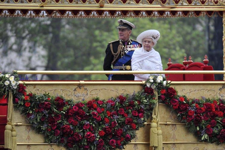 Felipe en traje militar con la Reina Isabel de pie en la plataforma dorada al aire libre